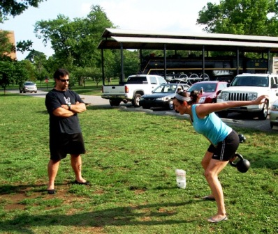 Nikki performing a snatch test with a 20kg with David Whitley, Sr RKC evaluating